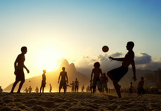 People kicking ball on beach