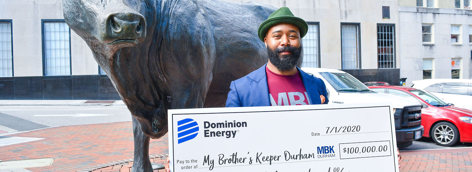 MBK Durham's Edmund Lewis stands in front of Bull in downtown with $100,000 check